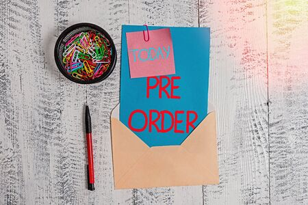 Conceptual hand writing showing Pre Order. Concept meaning an order for a product placed before it is available for purchase Envelope letter sticky note ballpoint clips on wooden background