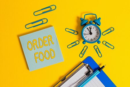 Handwriting text writing Order Food. Conceptual photo the process of requesting a preferred food in a restaurant Metal alarm clock clipboard clips ballpoint notepad colored background