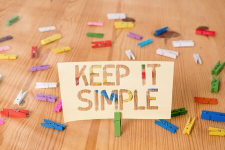 Text sign showing Keep It Simple. Business photo showcasing ask something easy understand not go into too much detail Colored clothespin papers empty reminder wooden floor background office Banque d'images