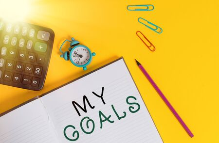 Word writing text My Goals. Business photo showcasing a future or desired result that a demonstrating commits to achieve Open striped notebook calculator clips pencil alarm clock color background