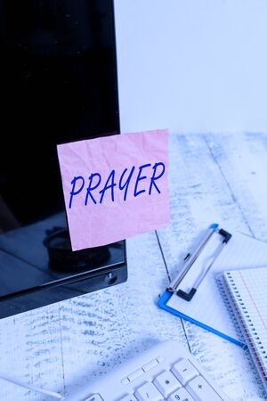 Text sign showing Prayer. Business photo text solemn request for help or expression of thanks addressed to God Note paper taped to black computer screen near keyboard and stationary