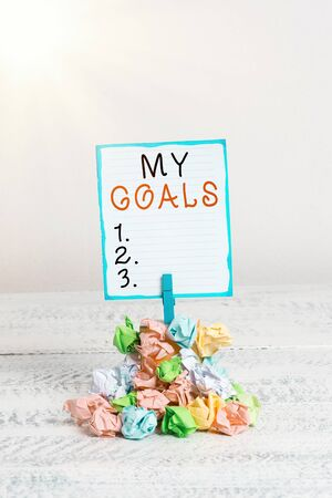 Handwriting text My Goals. Conceptual photo a future or desired result that a demonstrating commits to achieve Reminder pile colored crumpled paper clothespin reminder white wooden space Stock Photo