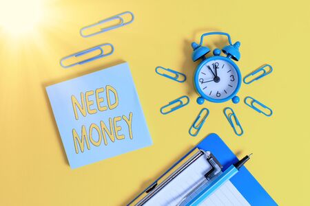 Handwriting text writing Need Money. Conceptual photo require a financial assistance to sustain spending or endeavor Metal alarm clock clipboard clips ballpoint notepad colored background