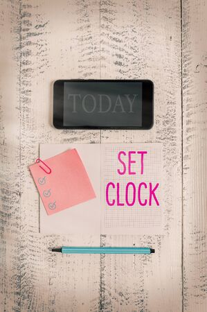 Conceptual hand writing showing Set Clock. Concept meaning put it to the right time or change the clock time to a later time Squared notebook marker smartphone sticky note wooden background