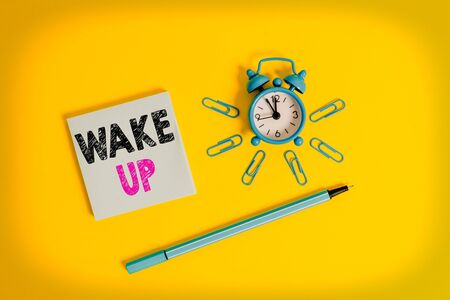Writing note showing Wake Up. Business concept for an instance of a demonstrating waking up or being woken up Rise up Metal alarm clock wakeup clips ballpoint notepad colored background