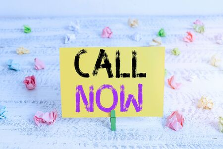 Text sign showing Call Now. Business photo showcasing To immediately contact a demonstrating using telecom devices with accuracy Green clothespin white wood background colored paper reminder office supply