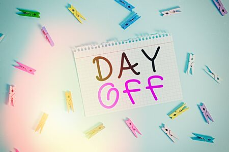 Writing note showing Day Off. Business concept for when you do not go to work even though it is usually a working day Colored clothespin rectangle shaped paper blue background