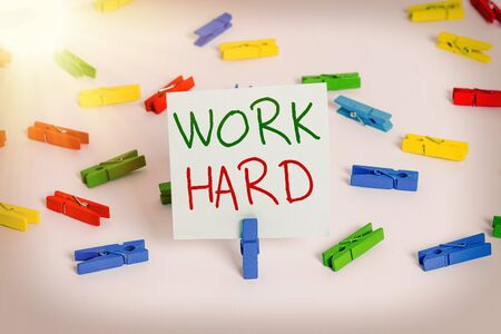Text sign showing Work Hard. Business photo showcasing Laboring that puts effort into doing and completing tasks Colored clothespin papers empty reminder white floor background office Stock Photo