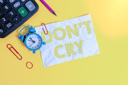 Handwriting text writing Don T Cry. Conceptual photo Shed tears typically as an expression of distress pain or sorrow Alarm clock clips note rubber band calculator pencil colored background