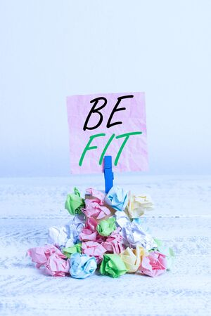 Conceptual hand writing showing Be Fit. Concept meaning of a suitable quality standard or type to meet the required purpose Reminder pile colored crumpled paper clothespin wooden space