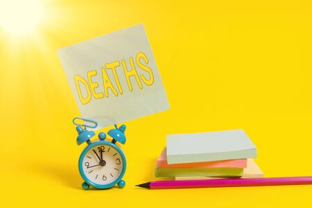 Text sign showing Deaths. Business photo text permanent cessation of all vital signs, instance of dying individual Alarm clock blank pencil sticky note stacked notepads colored background