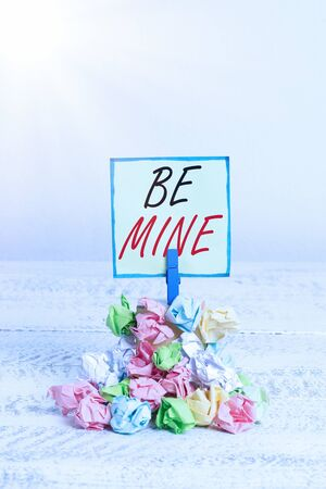 Conceptual hand writing showing Be Mine. Concept meaning like a demonstrating more than a friend and would like to date them Reminder pile colored crumpled paper clothespin wooden space