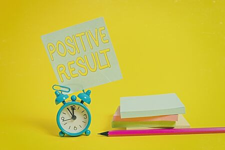 Text sign showing Positive Result. Business photo text shows that someone has the disease, condition, or biomarker Alarm clock blank pencil sticky note stacked notepads colored background