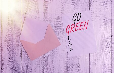 Handwriting text Go Green. Conceptual photo making more environmentally friendly decisions as reduce recycle Front view open colored envelope blank sheet letter paper wooden background