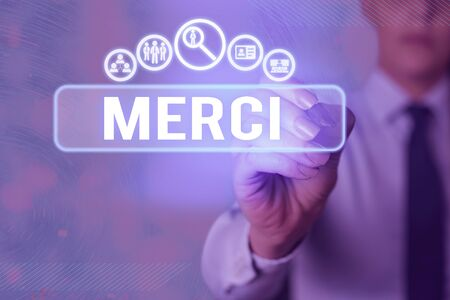 Writing note showing Merci. Business concept for what is said or response when someone helps you in France Thank you Foto de archivo