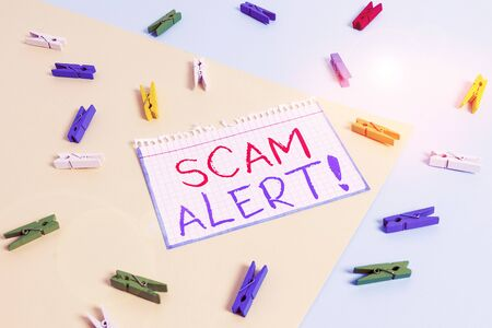 Writing note showing Scam Alert. Business concept for fraudulently obtain money from victim by persuading him Colored clothespin paper reminder with yellow blue background