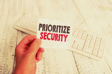 Writing note showing Prioritize Security. Business concept for designate security risk as more important to solve Man holding colorful reminder square shaped paper wood floor