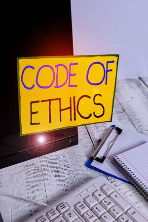 Word writing text Code Of Ethics. Business photo showcasing basic guide for professional conduct and imposes duties Note paper taped to black computer screen near keyboard and stationary 스톡 콘텐츠