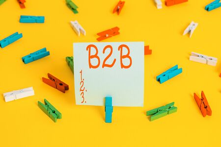 Word writing text B2B. Business photo showcasing Exchange of products services information between businesses E Commerce Colored clothespin papers empty reminder yellow floor background office Stok Fotoğraf