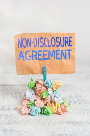 Text sign showing Non Disclosure Agreement. Business photo text Legal Contract Confidential Material or Information Reminder pile colored crumpled paper clothespin reminder white wooden space
