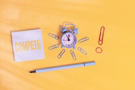 Conceptual hand writing showing Compete. Concept meaning win something by defeating or establishing superiority over others Alarm clock rubber band marker notepad colored background Banque d'images