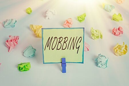 Conceptual hand writing showing Mobbing. Concept meaning Bulling of individual specially at work Emotional abuse Stress Colored crumpled paper empty reminder white floor clothespin