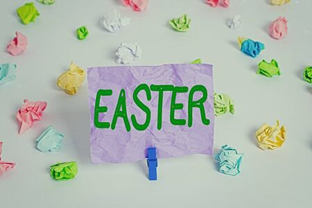 Word writing text Easter. Business photo showcasing the most important and oldest festival of the Christian Church Colored crumpled papers empty reminder white floor background clothespin