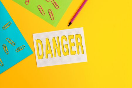 Word writing text Danger. Business photo showcasing the possibility of something unwelcome or unpleasant happening Blank paper sheets squared notebook pencil clips plain colored background