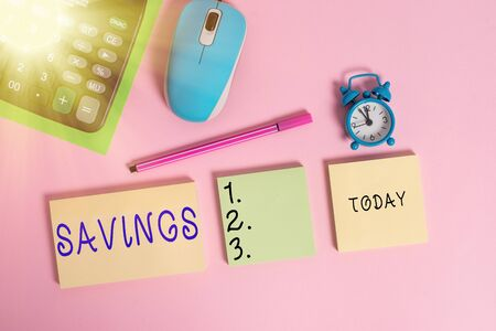 Text sign showing Savings. Business photo text the money that a demonstrating keeps in an account in a bank or like Notepads mouse alarm clock calculator sheet marker colored background Archivio Fotografico - 145455767