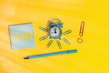 Conceptual hand writing showing Balance. Concept meaning a state of equilibrium or equipoise Living with peace and harmony Alarm clock rubber band marker notepad colored background