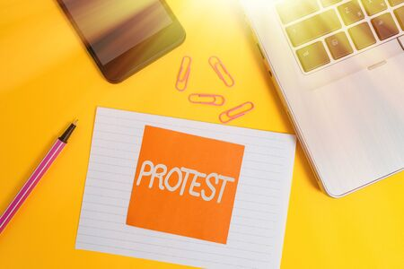 Handwriting text writing Protest. Conceptual photo An action expressing disapproval of or objection to something Trendy laptop smartphone marker paper sheet note clips colored background