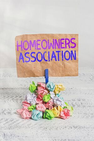 Text sign showing Homeowners Association. Business photo text Organization with fee for upkeeps of Gated Community Reminder pile colored crumpled paper clothespin reminder white wooden space