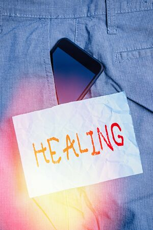 Text sign showing Healing. Business photo text process of making or becoming sound or healthy again Helping injured Smartphone device inside formal work trousers front pocket near note paper