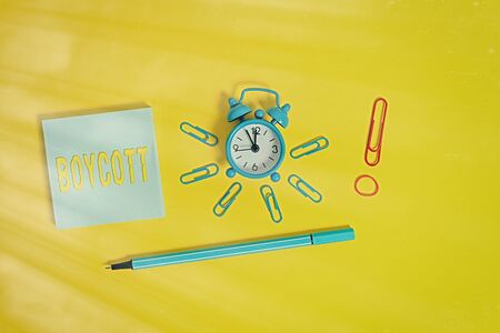 Conceptual hand writing showing Boycott. Concept meaning stop buying or using the goods or services of a certain company Alarm clock rubber band marker notepad colored background