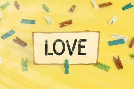 Conceptual hand writing showing Love. Concept meaning feeling of strong or constant affection for a demonstrating Feel deep romantic Colored clothespin papers empty reminder yellow floor office