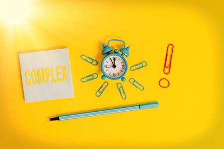 Conceptual hand writing showing Complex. Concept meaning the significant ideas that are completely or partly repressed Alarm clock rubber band marker notepad colored background