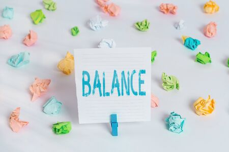Word writing text Balance. Business photo showcasing a state of equilibrium or equipoise Living with peace and harmony Colored crumpled papers empty reminder white floor background clothespin Фото со стока