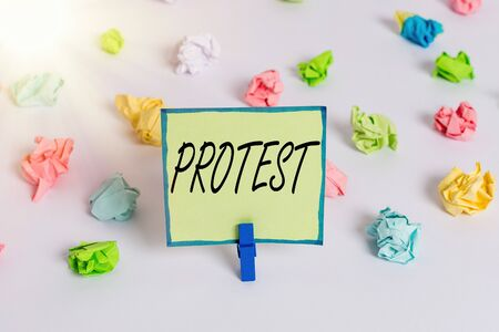 Conceptual hand writing showing Protest. Concept meaning An action expressing disapproval of or objection to something Colored crumpled paper empty reminder white floor clothespin