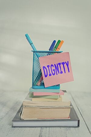 Handwriting text Dignity. Conceptual photo Quality Being worthy of honor respect Serious manner style Stacked books pens metal holder sticky note lying vintage old wooden table