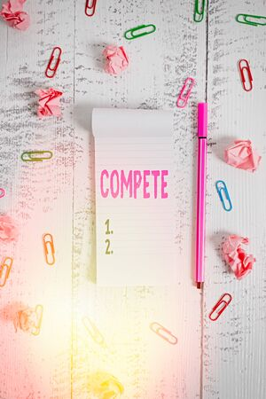 Word writing text Compete. Business photo showcasing win something by defeating or establishing superiority over others Stripped notepad clips paper balls pen lying wooden vintage background