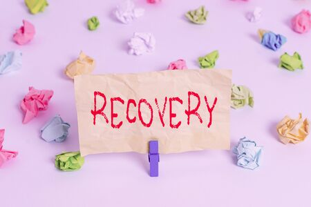 Text sign showing Recovery. Business photo showcasing the return to normal state of health mind or strength soon Colored crumpled papers empty reminder white floor background clothespin
