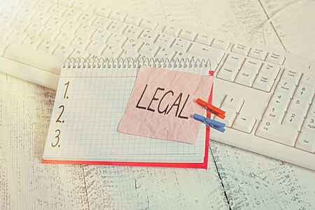 Handwriting text writing Legal. Conceptual photo Allowable or enforceable by being in conformity with the law notebook paper reminder clothespin pinned sheet white keyboard light wooden Stock Photo