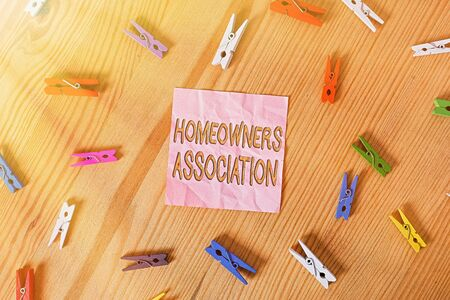 Word writing text Homeowners Association. Business photo showcasing Organization with fee for upkeeps of Gated Community Colored clothespin papers empty reminder wooden floor background office