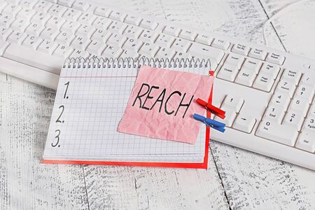 Handwriting text writing Reach. Conceptual photo the distance within which something can be touched or grabbed notebook paper reminder clothespin pinned sheet white keyboard light wooden