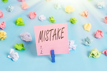Writing note showing Mistake. Business concept for Something not correct Lack of accuracy Wrong Incorrect Fail Colored crumpled papers empty reminder blue floor background clothespin