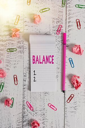Word writing text Balance. Business photo showcasing a state of equilibrium or equipoise Living with peace and harmony Stripped notepad clips paper balls pen lying wooden vintage background
