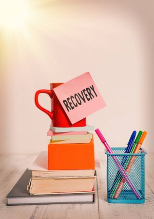 Writing note showing Recovery. Business concept for the return to normal state of health mind or strength soon Cup stacked note pad books on square box pens metal holder wooden table