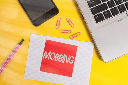 Handwriting text writing Mobbing. Conceptual photo Bulling of individual specially at work Emotional abuse Stress Trendy laptop smartphone marker paper sheet note clips colored background