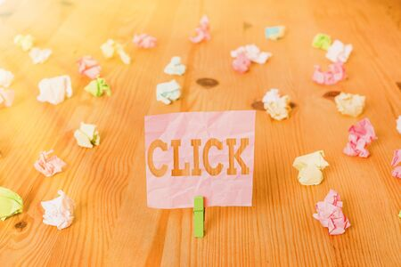 Text sign showing Click. Business photo showcasing Act of pressing a button on a mouse similar device Sharp short sound Colored crumpled papers empty reminder wooden floor background clothespin