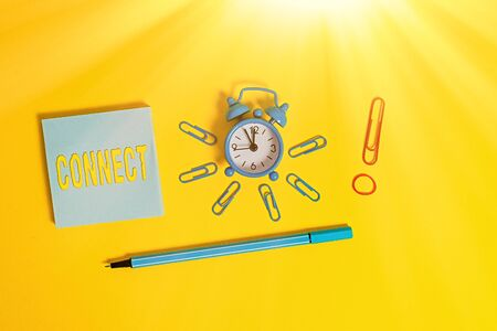 Conceptual hand writing showing Connect. Concept meaning Being together Contact Associate Relate Networking communicate Alarm clock rubber band marker notepad colored background